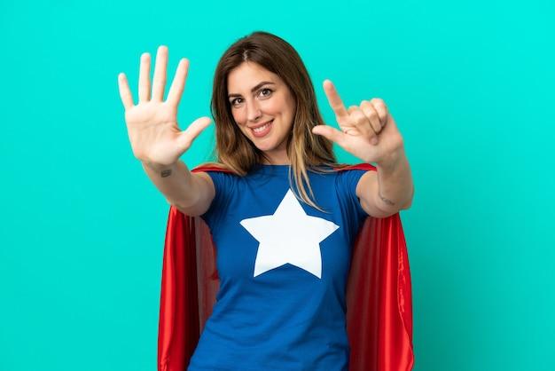 Kaukaska kobieta super hero na białym tle na niebieskim tle, licząc siedem palcami