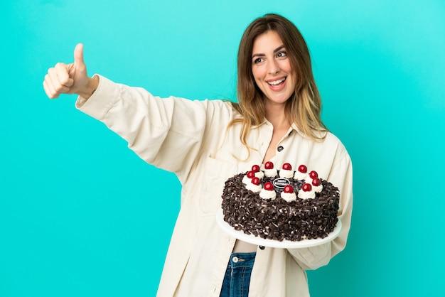 Kaukaska kobieta trzyma tort urodzinowy na białym tle na niebieskim tle dając gest kciuka w górę
