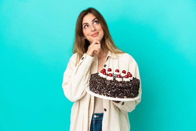Kaukaska kobieta trzyma tort urodzinowy na białym tle na niebieskim tle i patrząc w górę