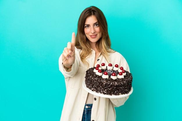 Kaukaska kobieta trzyma tort urodzinowy na białym tle na niebieskim tle pokazując i podnosząc palec