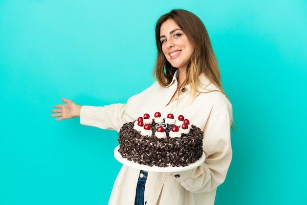 Kaukaska kobieta trzyma tort urodzinowy na białym tle na niebieskim tle wyciągając ręce do boku za zaproszenie do przyjścia