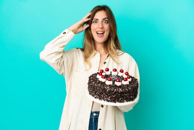 Kaukaska kobieta trzyma tort urodzinowy na białym tle na niebieskim tle z wyrazem niespodzianki