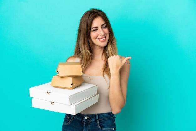 Kaukaska kobieta trzymająca pizze i burgera na białym tle na niebieskim tle wskazująca na bok, aby zaprezentować produkt