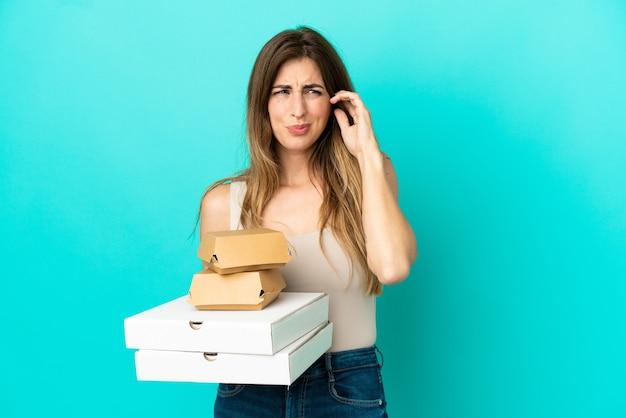 Kaukaska kobieta trzymająca pizze i hamburgera na niebieskim tle sfrustrowana i zakrywająca uszy