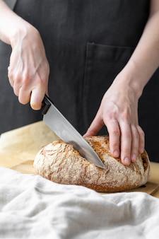 Kaukaska kobieta trzymająca świeży chleb z pieca piecze domowy chleb