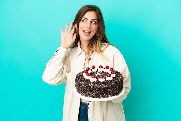 Kaukaska kobieta trzymająca tort urodzinowy na białym tle na niebieskim tle, słuchając czegoś, kładąc rękę na uchu