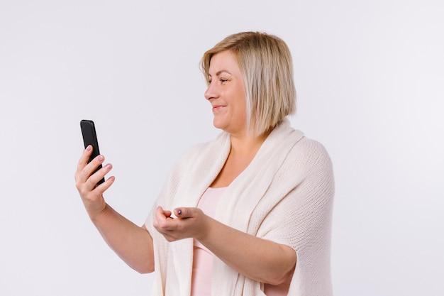 Kaukaska kobieta uśmiecha się i komunikuje się za pomocą komunikacji wideo. białe tło. zdjęcie profilowe. wysokiej jakości zdjęcie