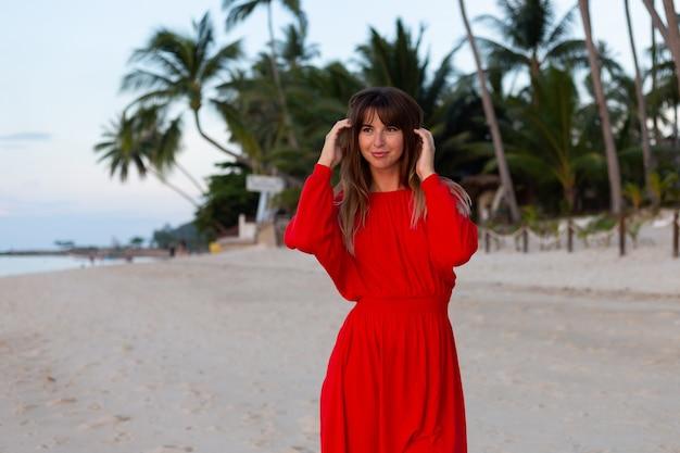 Kaukaska kobieta w czerwonej letniej sukience w romantycznym szczęśliwym nastroju na tropikalnej białej piaszczystej plaży o zachodzie słońca