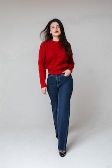 Kaukaska kobieta w czerwonym swetrze i niebieskich dżinsach trzyma rękę w kieszeni i spaceruje