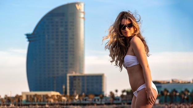 Kaukaska kobieta w okularach przeciwsłonecznych i stroju kąpielowym pozuje na wybrzeżu morza śródziemnego, hiszpania