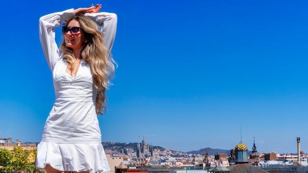 Kaukaska kobieta w okularach przeciwsłonecznych pozuje z widokiem na barcelonę w tle, hiszpania