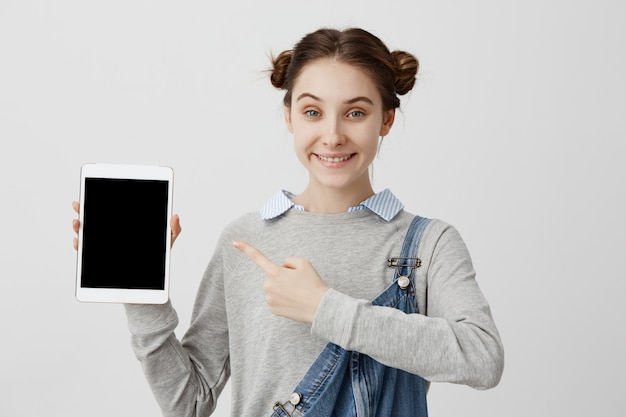 Kaukaska kobieta w przypadkowym drelichu demonstruje nowożytne modne techniki w jej ręce z uśmiechem. headshot zadowolonej klientki zadowolonej z długo oczekiwanego zakupu. marketing, sprzedaż