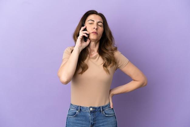 Kaukaska kobieta w średnim wieku korzystająca z telefonu komórkowego odizolowanego na fioletowym tle, cierpiąca na ból pleców za wysiłek