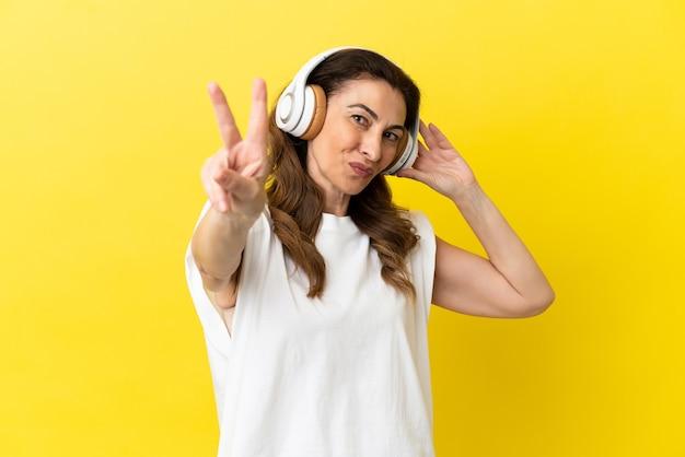 Kaukaska kobieta w średnim wieku na żółtym tle słuchając muzyki i śpiewając