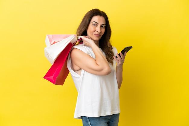 Kaukaska kobieta w średnim wieku na żółtym tle trzyma torby na zakupy i pisze wiadomość telefonem komórkowym do przyjaciela