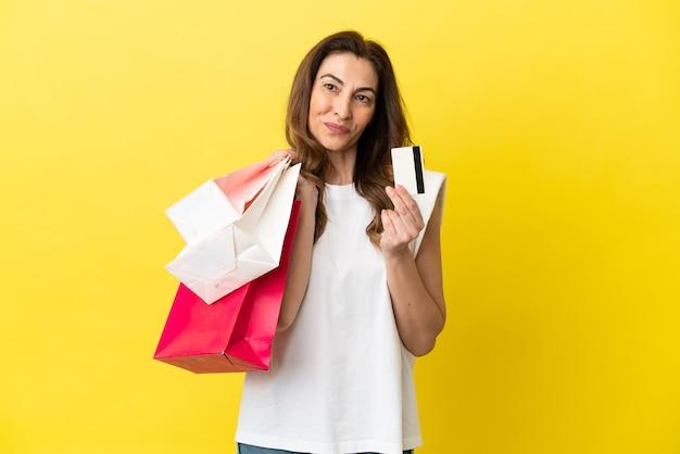 Kaukaska kobieta w średnim wieku na żółtym tle trzymająca torby na zakupy i kartę kredytową