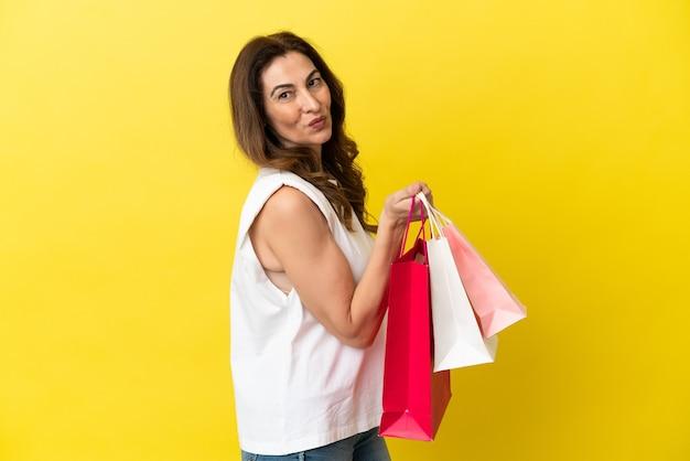 Kaukaska kobieta w średnim wieku na żółtym tle trzymająca torby na zakupy i uśmiechnięta