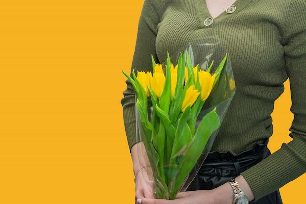 Kaukaska kobieta w zielonej bluzce trzyma bukiet żółci tulipany. prezent na święta.