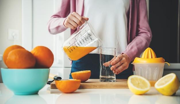 Kaukaska kobieta w zwykłym ubraniu nalewa sok do szklanki po wyciśnięciu z cytryn i pomarańczy