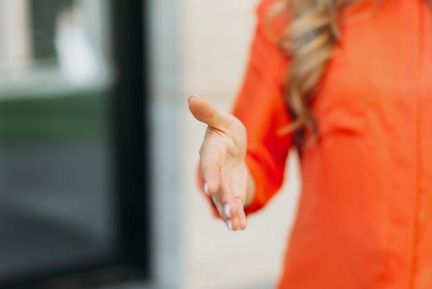 Kaukaska kobieta wyciąga rękę na znak powitania lub przywitania.