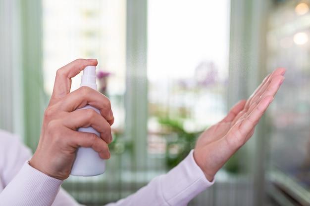 Kaukaska kobieta wyciera ręce sprayem do mycia rąk na bazie alkoholu. środki zapobiegawcze przeciwko infekcji żelem do dezynfekcji rąk.