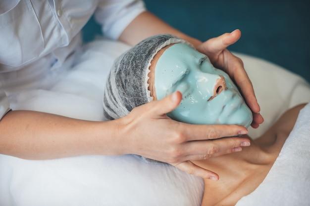 Kaukaska kobieta z czapką medyczną ma zabieg na twarz, nosząc maskę w salonie spa