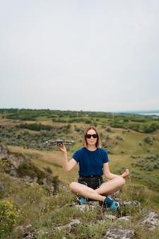 Kaukaska kobieta z dronem w dłoni, siedząca na zielonym skalistym wzgórzu z niebem