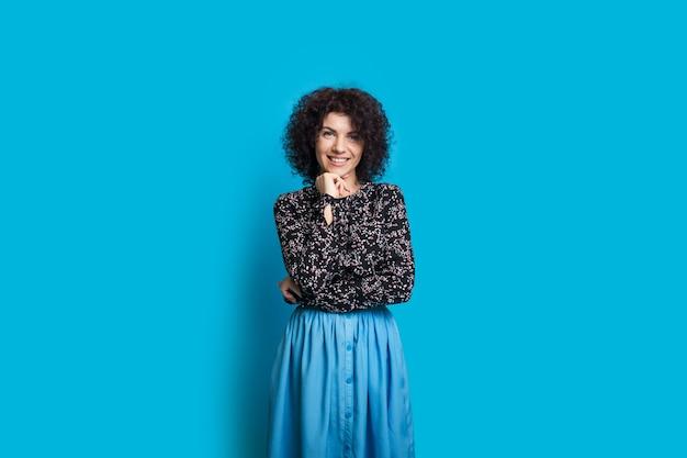 Kaukaska kobieta z kręconymi włosami dotyka jej brody, uśmiechając się do kamery i pozując na niebieskiej ścianie