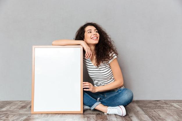 Kaukaska kobieta z pięknym włosy pozuje z krzyżować nogami demonstruje dużego wielkiego obraz lub portret odizolowywających nad szarości ściany kopii przestrzenią