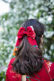 Kaukaska kobieta z pięknymi falującymi włosami i kokardką przed kwitnącym wiosną drzewem