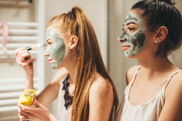 Kaukaska kobieta z rudymi włosami i jej przyjaciółka brunetka nakładają maskę przeciwtrądzikową na twarz patrząc w lustro