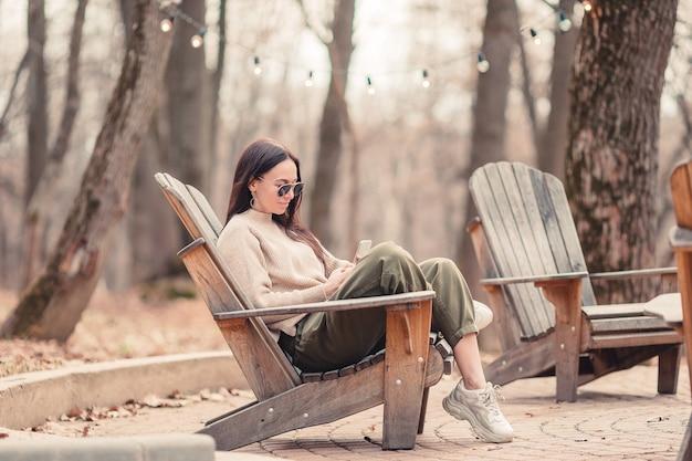 Kaukaska kobieta z telefonem komórkowym outdoors w kawiarni. dziewczyna za pomocą smartfona.