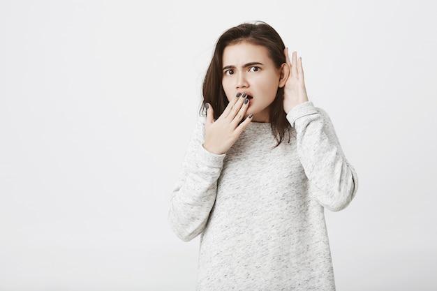Kaukaska kobieta z zszokowanym wyrazem twarzy, zakrywająca usta i trzymająca rękę przy uchu, aby usłyszeć plotki