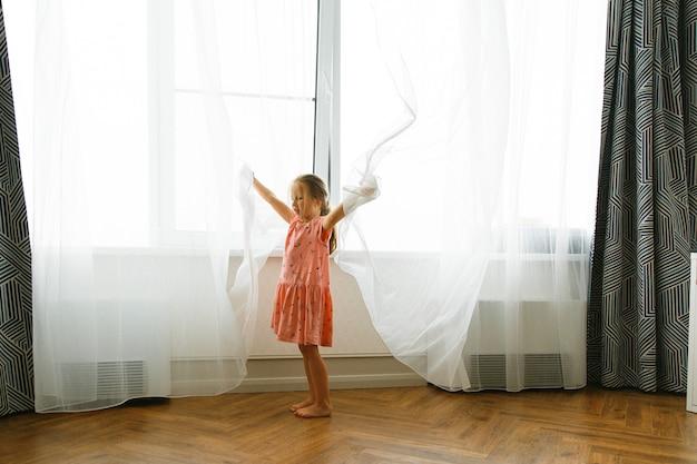 Kaukaska mała dziewczynka gra w chowanego z zasłonami w pokoju przy oknie