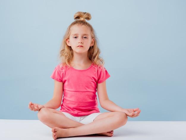Kaukaska mała dziewczynka siedzi w pozycji jogi na niebiesko