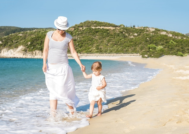 Kaukaska matka spacerująca po plaży z córką w ciągu dnia