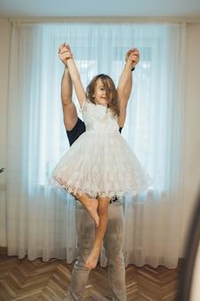 Kaukaska matka trzyma córkę w białej sukni, udając baletnicę i patrząc na przód