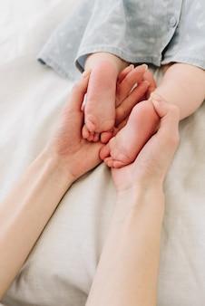 Kaukaska matka trzyma stopy jej małej córeczki