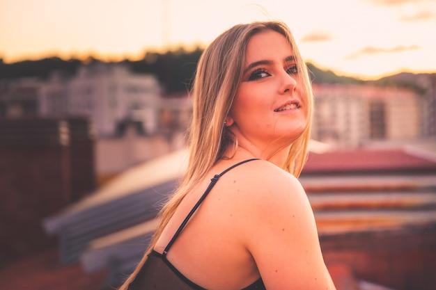Kaukaska młoda dziewczyna pozuje podczas zachodu słońca na dachu z ładnym widokiem na donostia-san sebastian, kraj basków.