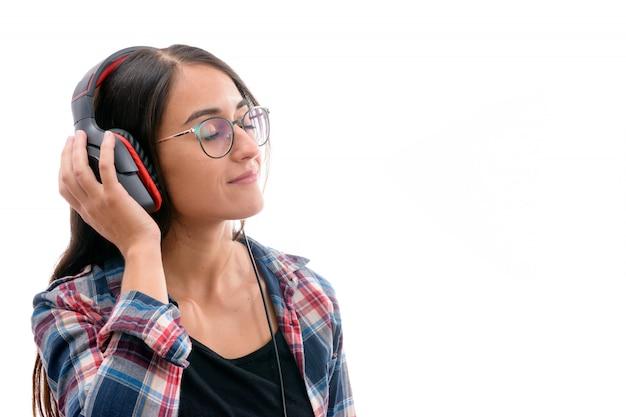 Kaukaska młoda dziewczyna słucha muzyka z dużymi hełmofonami odizolowywającymi na białym tle