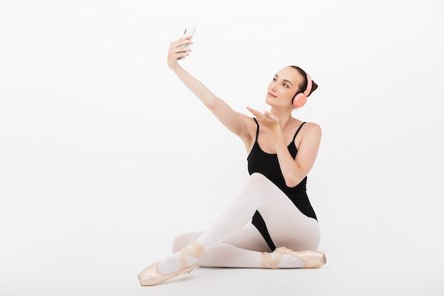 Kaukaska młoda kobieta balerina w słuchawkach robi zdjęcie selfie na telefonie komórkowym izolowanym na tle białej ściany
