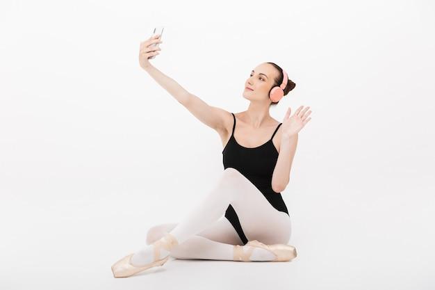 Kaukaska Młoda Kobieta Balerina W Słuchawkach Robi Zdjęcie Selfie Na Telefonie Komórkowym Izolowanym Na Tle Białej ściany Premium Zdjęcia