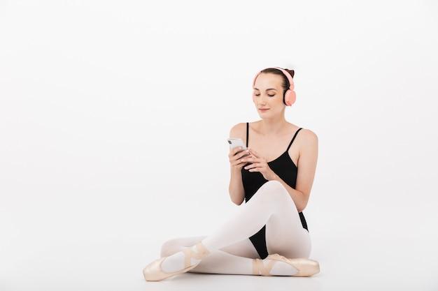 Kaukaska młoda kobieta baletnica słuchająca muzyki z telefonem komórkowym i słuchawkami izolowanymi na tle białej ściany
