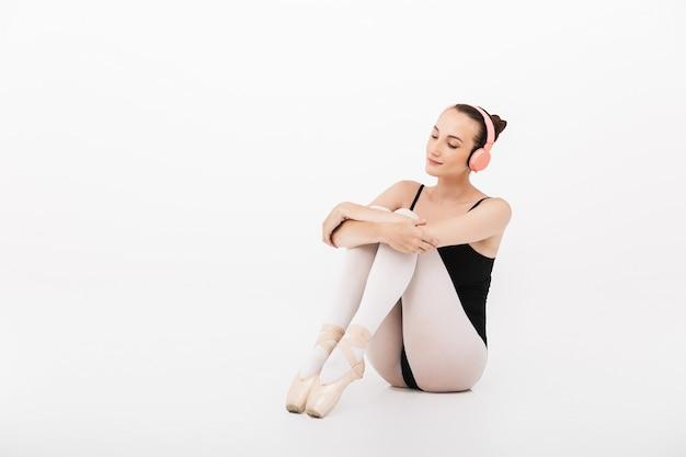 Kaukaska młoda kobieta baletnica słuchająca muzyki ze słuchawkami izolowanymi na tle białej ściany