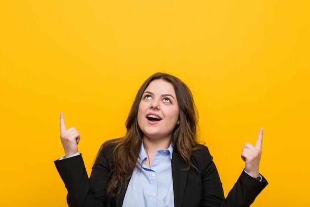 Kaukaska młoda kobieta biznesu plus size wskazuje palcami u góry pokazując pustą przestrzeń