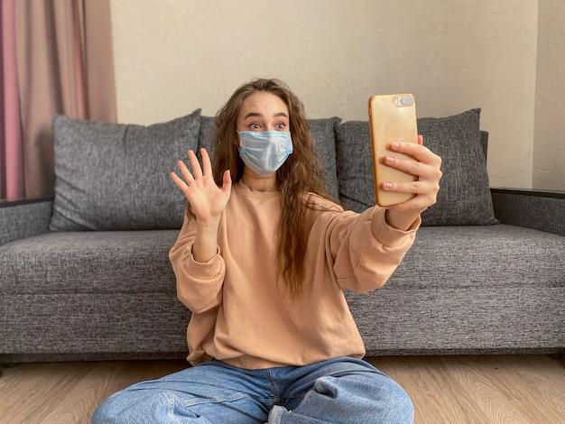 Kaukaska młoda kobieta jest ubranym medyczną maskę siedzi w domu na samoizolaci podczas pandemii koronawirusa.