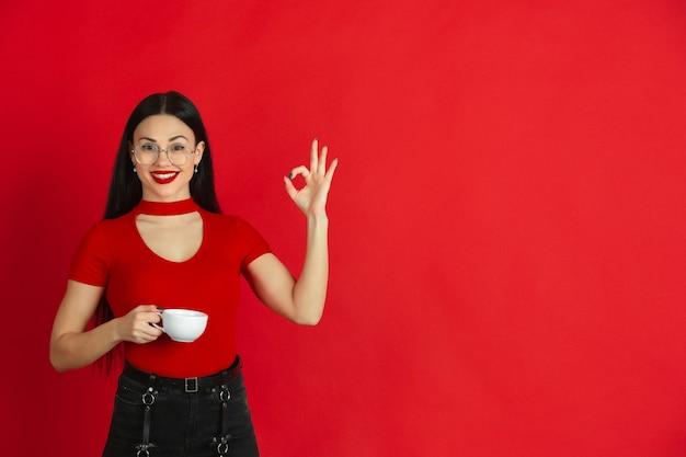 Kaukaska młoda kobieta monochromatyczny portret na czerwonej ścianie emocjonalny i ekspresyjny