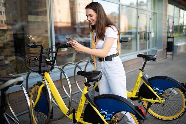 Kaukaska młoda kobieta płaci za wypożyczenie roweru w aplikacji