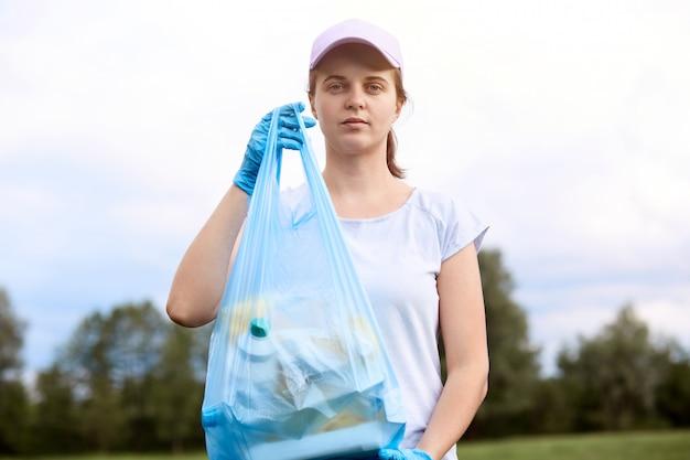 Kaukaska młoda kobieta podnosi śmieci od łąki. kobiece pole do sprzątania, zbieranie śmieci do worka na śmieci, noszenie koszulki i czapki z daszkiem, stojący z drzewami i niebem