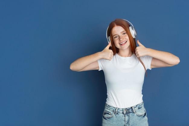 Kaukaska młoda kobieta słucha muzyki na niebieskiej ścianie